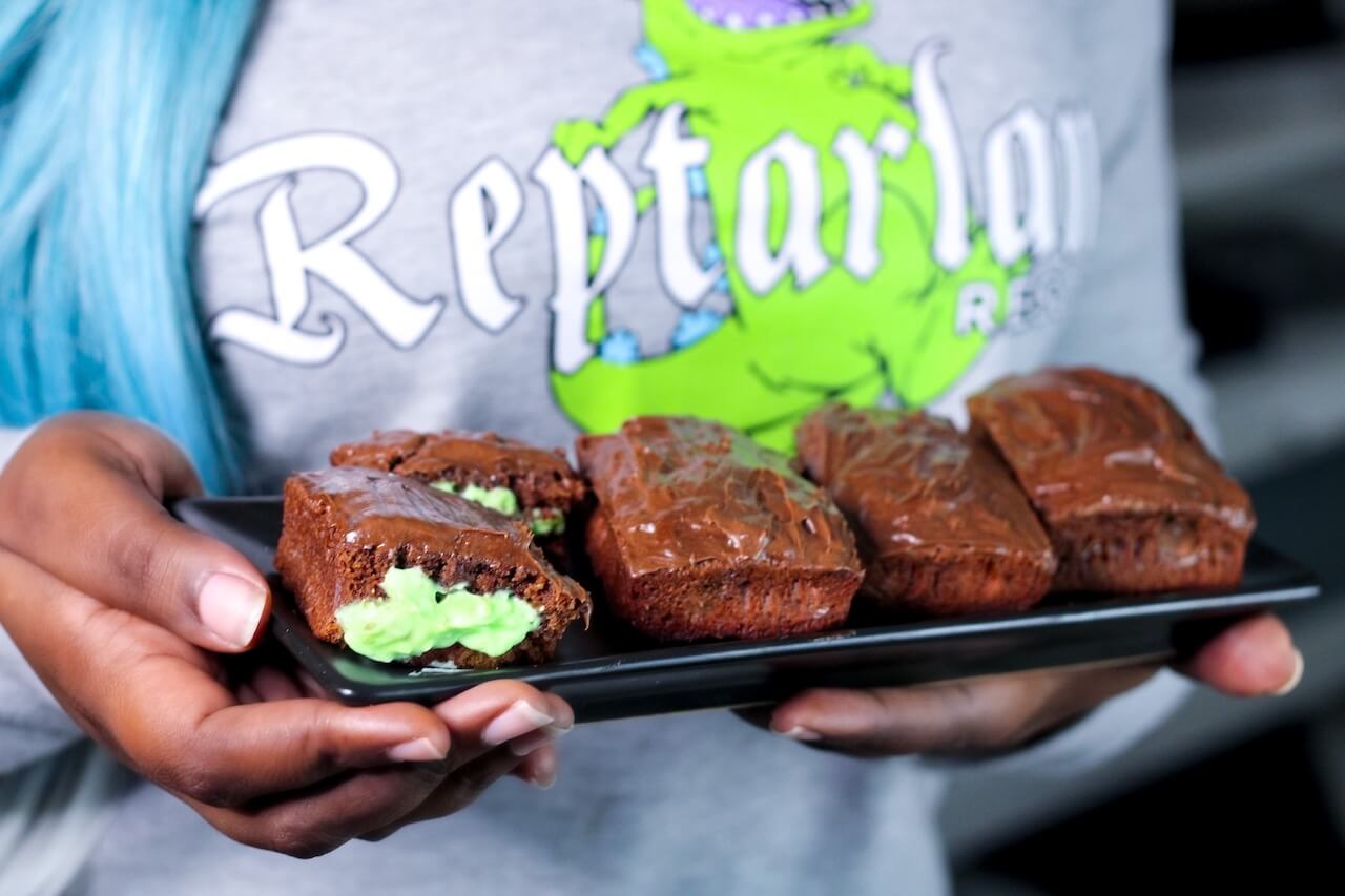 """Erika holding a plate of chocolate brownies. The left most brownie is cut in half to reveal green frosting. She is wearing a shirt with an image of Reptar that reads """"Reptarland."""""""